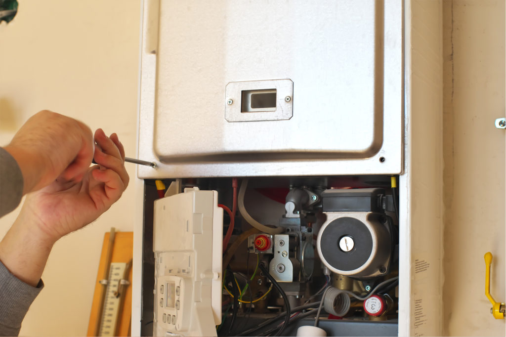 an gas engineer using a screwdriver whilst working on combi boilers