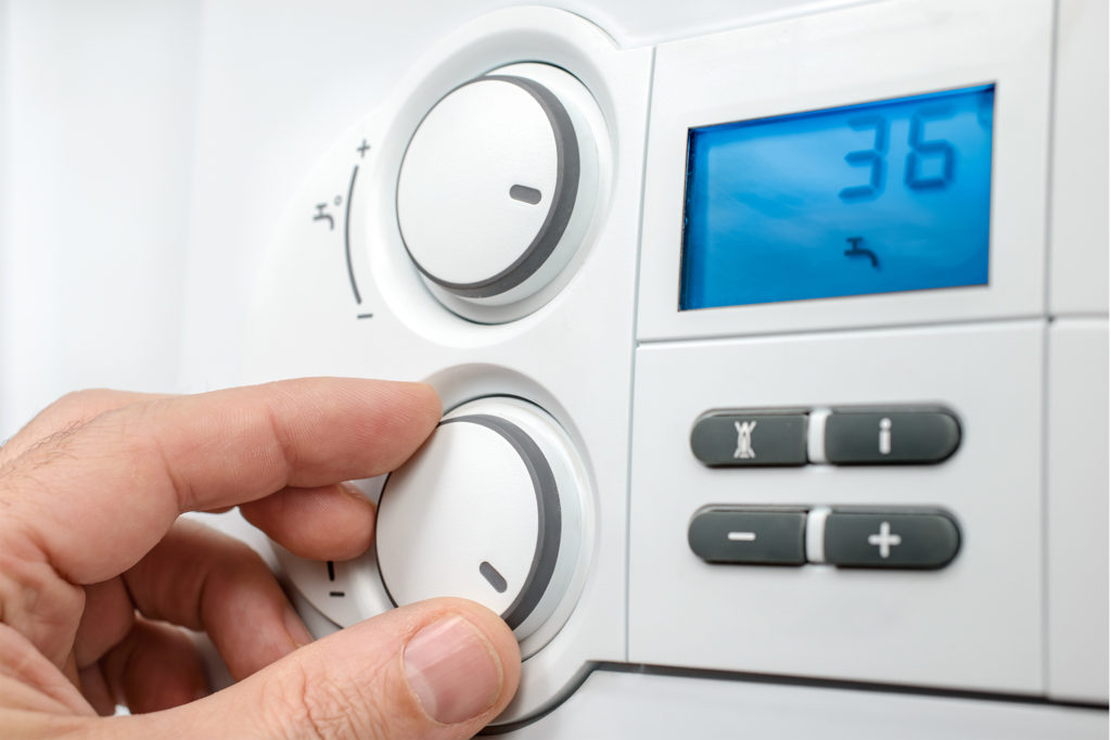 a hand adjusting a dial on a modern combi boiler would benefit from a guide to your combi