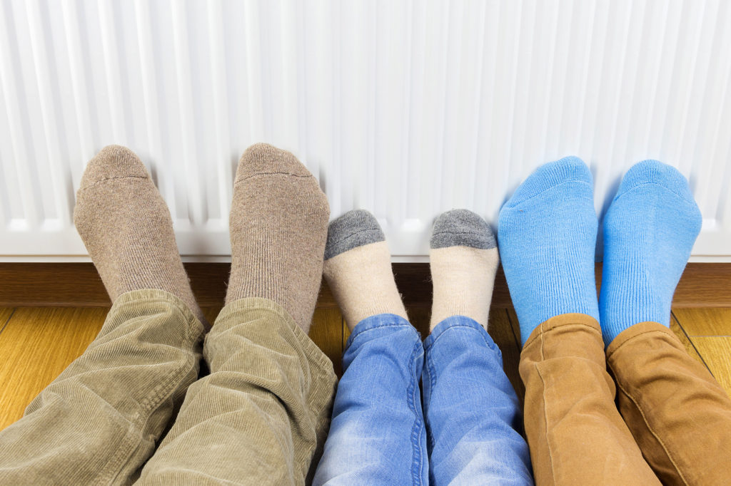 three pairs of feet in front of a radiator making the most out of heating your home