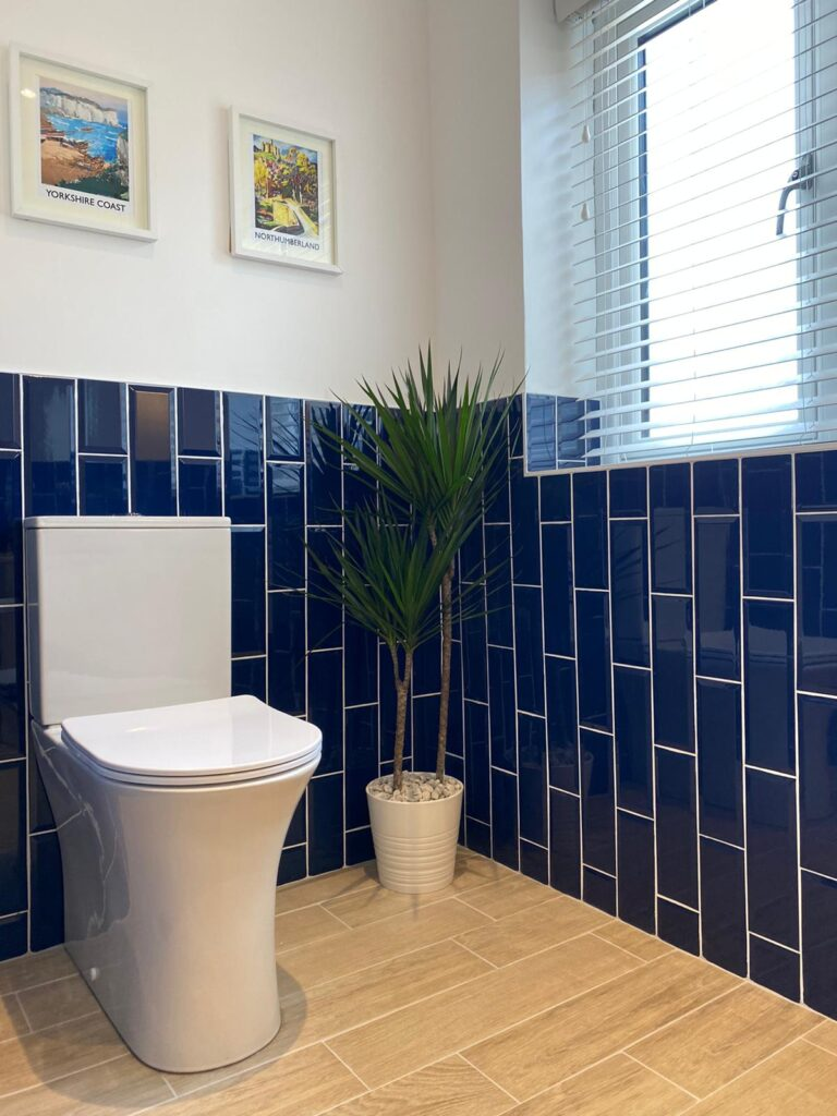 kitchen to bedroom conversion new toilet with blue vertical brick style gloss tiles and feature indoor plant in corner with pictures on wall and window