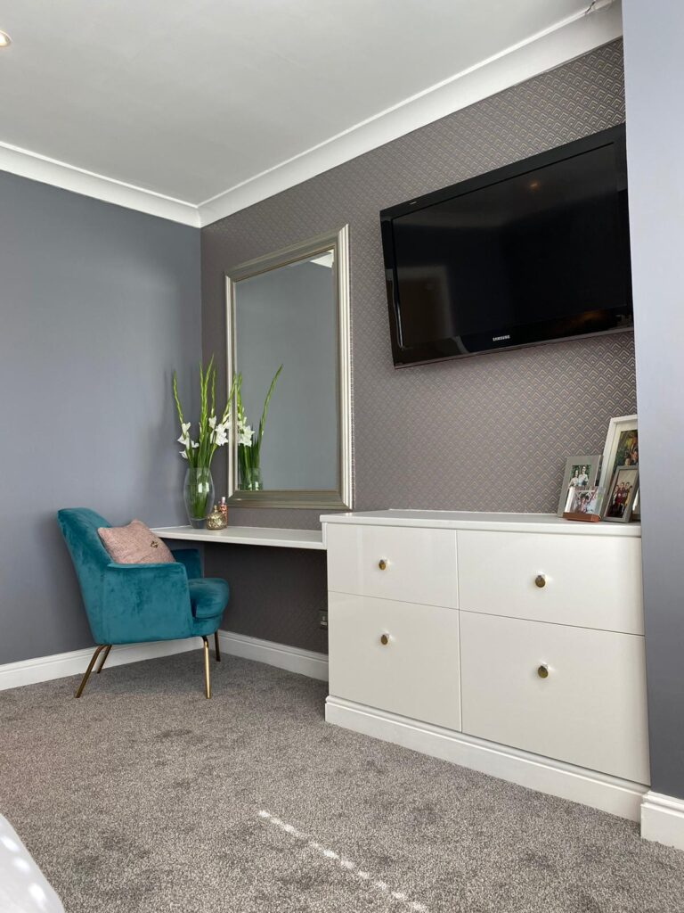 kitchen to bedroom conversion bedroom dressing table and luxury blue chair with large wall mirror and wall mounted t.v.
