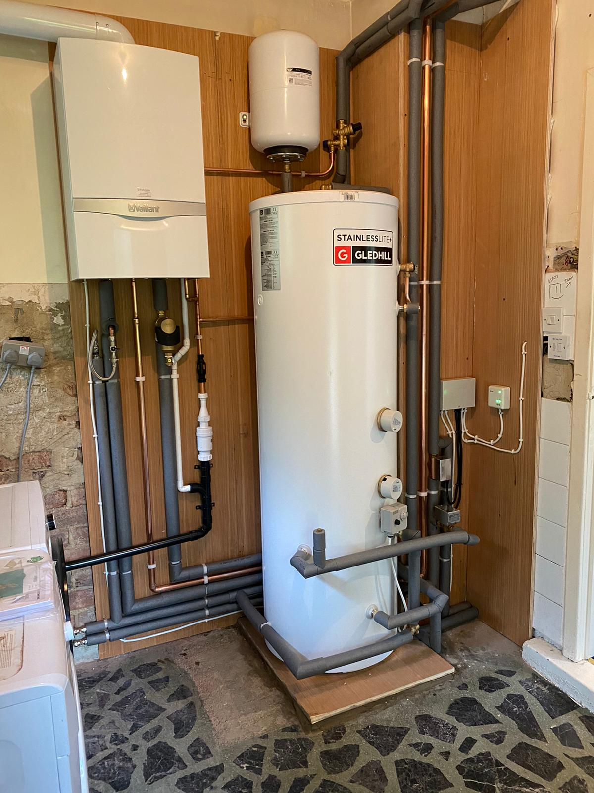 Complete heating system fitted including Vaillant Ecotec Plus, Gledhill unvented cylinder with remote expansion vessel, system zone valves and wiring. all pipework clipped to plywood back and covered in pipe insulation where appropriate