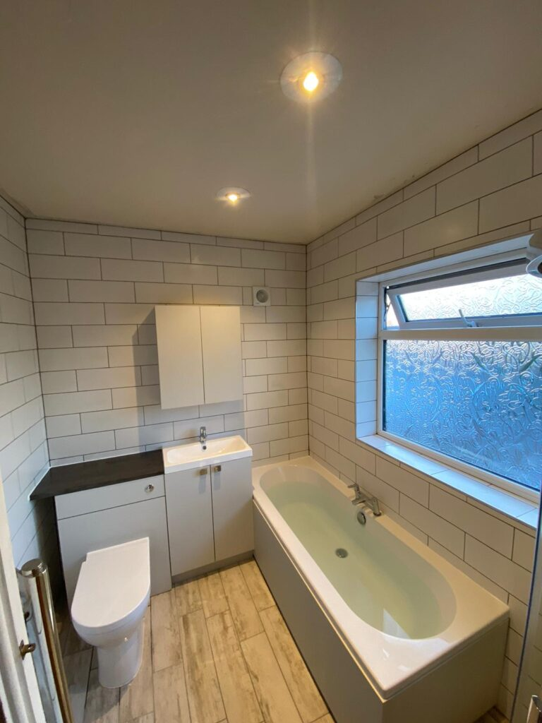full bathroom suite with vanity cupboard and tessellating floor to ceiling white tiles
