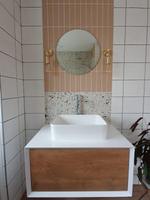 Straight swap bathroom front view of vanity unit complete, comprising of a white and wood effect cupboard and sink mounted on top with mono-mixer tap. 2 types of tiles and mirror with wall mounted pendant lighting.