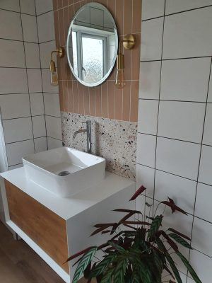 Straight swap bathroom door view of vanity unit complete, comprising of a white and wood effect cupboard and sink mounted on top with mono-mixer tap. 2 types of tiles and mirror with wall mounted pendant lighting.