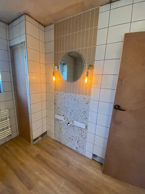 Straight swap bathroom vanity unit wall tiling complete with 2 types of tiles and mirror with wall mounted pendant lighting.
