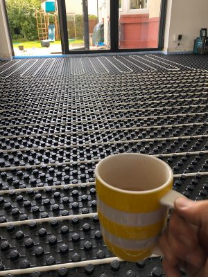 scale image of nu-heat underfloor heating pipework along side a cup of tea