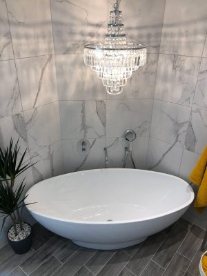 Bath and chandelier feature in luxury bathroom conversion from bedroom by Parkstone Yorkshire