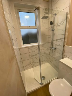 Narrow bathroom large shower cubicle with floor to ceiling mable effect tiles.