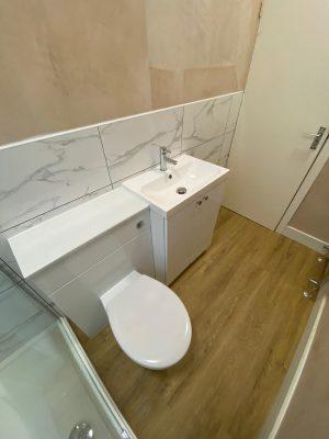 Narrow bathroom marble style tiles and Polyflor oak floor finish