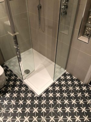 Bathroom renovation new walk in shower cubicle set into floor alonside black and white tiles