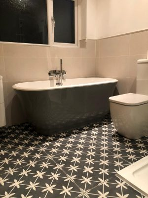 Bathroom renovation free standing bath and toilet on black and white tiles with underfloor heating.