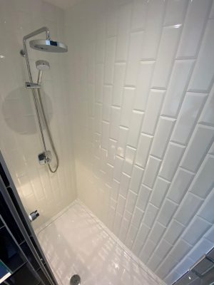 kitchen to bedroom conversion inside shower cubicle with large pan head shower and white vertical brick tiling
