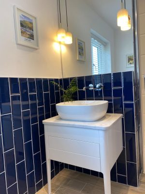 kitchen to bedroom conversion basin on table in front of blue gloss vertical brick style tiles with mirror and hanging lights