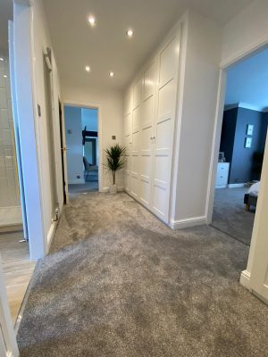 kitchen to bedroom conversion walk in wardrobe with luxury grey carpet and built in wardrobes