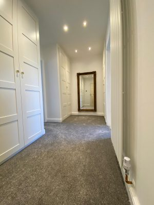 kitchen to bedroom conversion walk in wardrobe with grey carpet and vertical designer radiator and full length mirror