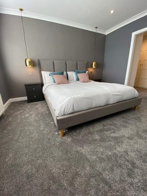 kitchen to bedroom conversion bedroom with grey carpet and gold ceiling mounted bedside lights