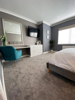 kitchen to bedroom conversion bedroom dressing table and luxury blue chair with large wall mirror and bedroom window