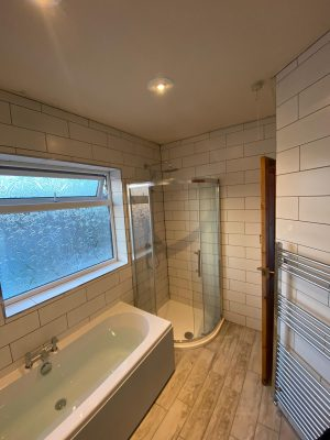 new bath, curved shower cubicle and white tessellating tiles
