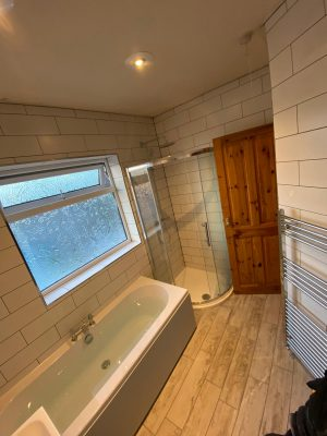 new bath, curved shower cubicle and white tessellating tiles and bathroom door open
