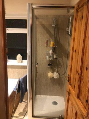 view through bathroom door to old shower cubicle