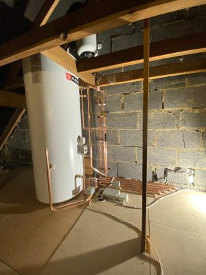 unvented hot water cylinder with exposed pipework and components in loft space.