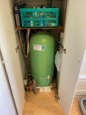 old indirect hot water cylinder in airing cupboard before upgrade to unvented hot water