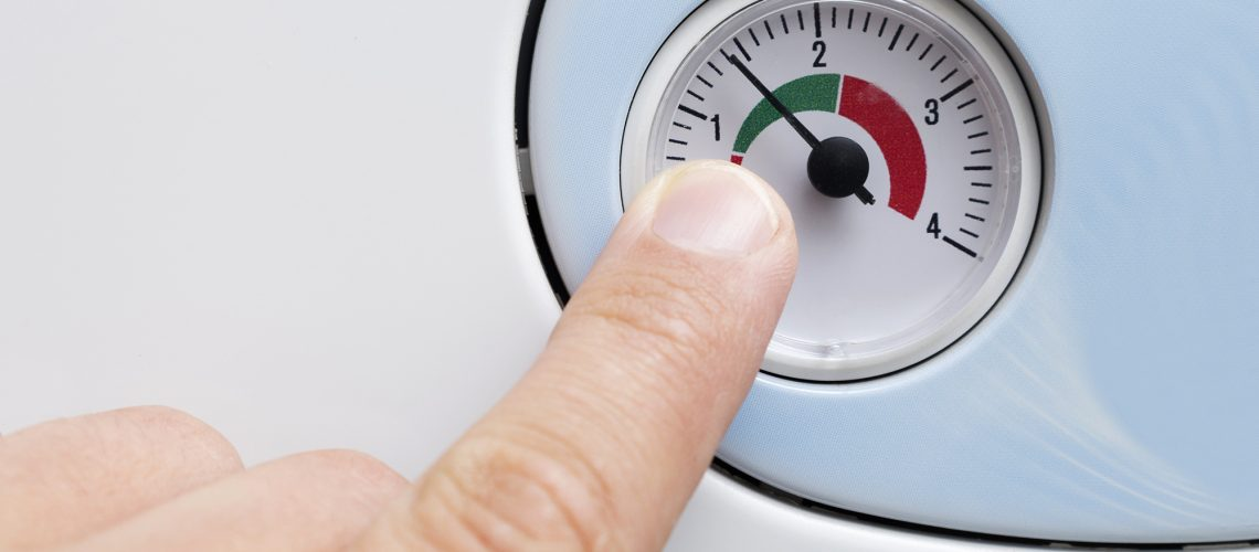 a finger points to a gauge which tells you when you need to re-pressurise your central heating system